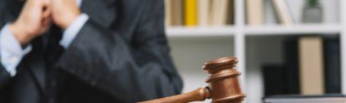 abogado-sexo-masculino-que-sienta-detras-mazo-juez-tabla-madera_23-2147898252