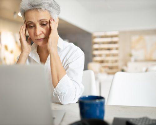 senior-mujer-triste-cabello-gris-trabajando-computadora-portatil-frotandose-ojos-u-ocultando-lagrimas-llena-pensamientos-inquietos_343059-3737